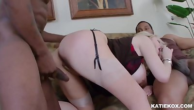 White slut is playing with her big tits together with black cocks, surrounding the living room